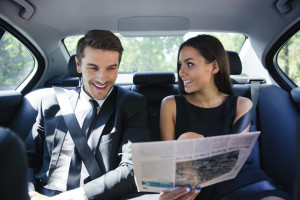 Couple reading newspaper in car